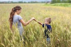 Mujer joven y niño pequeño su hijo que se coloca en campo de trigo uni Foto de archivo libre de regalías