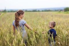 Mujer joven y niño pequeño su hijo que se coloca en campo de trigo uni Imagen de archivo libre de regalías