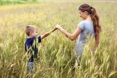 Mujer joven y niño pequeño su hijo que se coloca en campo de trigo uni Foto de archivo