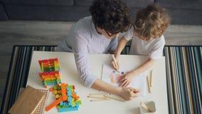 Mujer joven y niño que dibujan junto la fabricación de la imagen con los lápices en plano metrajes