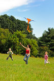 Mujer joven y niños que vuelan una cometa imagen de archivo libre de regalías
