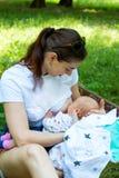 Mujer joven y nueva madre que amamantan al bebé recién nacido afuera en el parque, mamá bonita que se considera infantil en manos imagenes de archivo