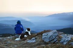 Mujer joven y perro que admiran alto de la salida del sol en la montaña Imagen de archivo libre de regalías