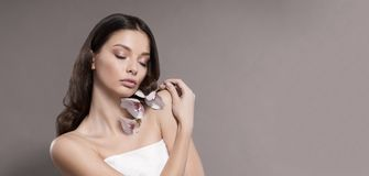 Mujer joven y sana con el maquillaje ligero que sostiene la flor de la orquídea Fondo beige Imagen de archivo