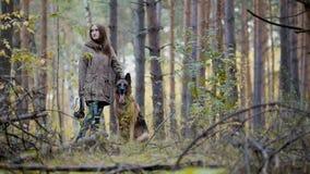 Mujer joven y su animal doméstico - pastor alemán - que caminan en un bosque del otoño Imagen de archivo libre de regalías