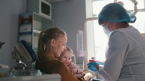 Mujer joven y su hija en la consulta con el dentista, ellos que juegan y que ríen almacen de video