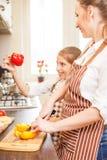 Mujer joven y su hija que cocinan junto Fotos de archivo libres de regalías