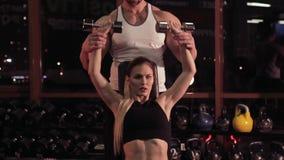 Mujer joven y su instructor personal de la aptitud en el gimnasio con pesas de gimnasia almacen de metraje de vídeo