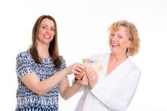 Mujer joven y su madre con el dinero Fotos de archivo