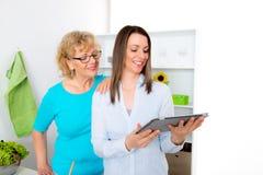 Mujer joven y su madre junto en la cocina y la etiqueta con Imagenes de archivo