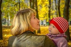 Mujer joven y su pequeña hija en el parque del otoño Imagenes de archivo