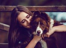 Mujer joven y su perro del collie en parque fotografía de archivo libre de regalías