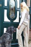 Mujer joven y su perro delante de la casa. Imagen de archivo libre de regalías
