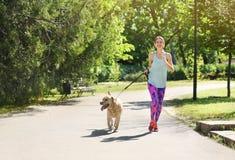 Mujer joven y su perro que pasan el tiempo junto al aire libre Animal doméstico care Fotos de archivo