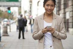 Mujer joven y teléfono elegante que caminan en la calle Imagen de archivo libre de regalías
