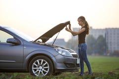 Mujer joven y un coche con la capilla hecha estallar Transporte, problemas de los vehículos y concepto de las averías fotografía de archivo