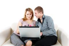 Mujer joven y un hombre con un ordenador portátil Fotos de archivo