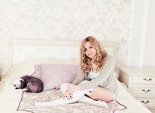 Mujer joven y un perro que se sienta en una cama Foto de archivo libre de regalías
