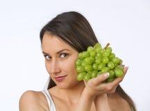Mujer joven y uvas frescas Foto de archivo libre de regalías