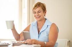 Mujer jubilada mayor alegre que usa el teléfono móvil foto de archivo