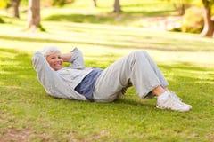 Mujer jubilada que la hace estiramientos en el parque Foto de archivo libre de regalías