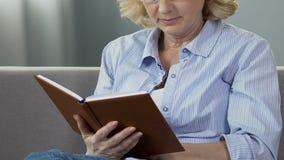 Mujer jubilada que se sienta en el sofá y el libro de lectura, lector ávido del libro, tiempo libre almacen de metraje de vídeo