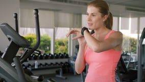 Mujer juguetona activa apta que hace ejercicios en velosimulator Usando su smartwatch, enviando el mensaje al amigo almacen de video
