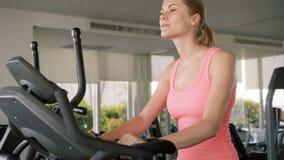 Mujer juguetona activa apta que hace ejercicios en velosimulator Usando su smartwatch que comprueba vitals almacen de video