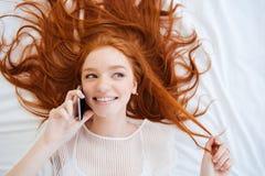 Mujer juguetona alegre que habla en el teléfono celular en cama Imagen de archivo