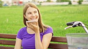 Mujer juguetona con la bici que habla en el teléfono móvil Hembra joven que tiene conversación casual sobre el teléfono elegante almacen de metraje de vídeo