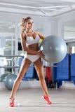 Mujer juguetona con la bola en el gimnasio Fotos de archivo libres de regalías