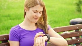 Mujer juguetona de la cámara lenta con la bici que manda un SMS en el reloj elegante en parque Usando su smartwatch, mensajería almacen de video