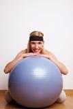 Mujer juguetona detrás de la bola de la gimnasia Fotos de archivo libres de regalías