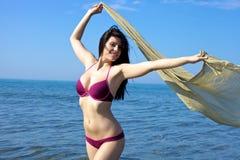 Mujer juguetona en el mar con el cuerpo imponente que se divierte con velo en vacaciones Fotos de archivo