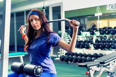 Mujer juguetona hermosa en la ropa de deportes que hace ejercicio con un hea Imagenes de archivo