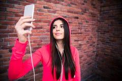 Mujer juguetona joven feliz que hace la foto del selfie Foto de archivo libre de regalías