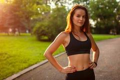 Mujer juguetona joven que mira la cámara después de entrenamiento en parque del verano sportswear Mujer fuerte que tiene resto imagen de archivo