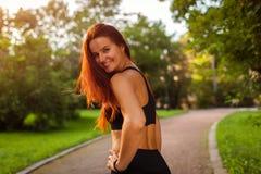 Mujer juguetona joven que mira la cámara después de entrenamiento en parque del verano sportswear Mujer fuerte que tiene resto fotos de archivo libres de regalías