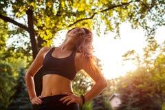 Mujer juguetona joven que se enfría después de entrenamiento en parque del verano sportswear Mujer fuerte que tiene resto foto de archivo libre de regalías