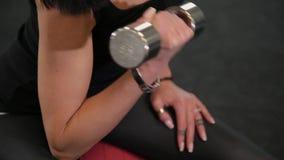 Mujer juguetona joven que se sienta en bola apta y pesas de gimnasia de elevación mientras que entrena al bíceps en gimnasio almacen de metraje de vídeo
