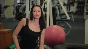 Mujer juguetona joven que se sienta en bola apta y pesas de gimnasia de elevación mientras que entrena al bíceps en gimnasio metrajes