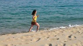 Mujer juguetona que corre en la playa almacen de metraje de vídeo