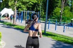 Mujer juguetona que corre a lo largo de la trayectoria cerca de patio del deporte Imagenes de archivo