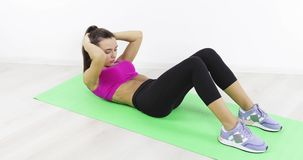 Mujer juguetona que hace ejercicios del ABS para tener vientre plano metrajes