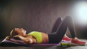 Mujer juguetona que hace el entrenamiento intenso de la aptitud en el gimnasio Atleta de sexo femenino en la ropa de deportes, a  almacen de video