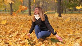 Mujer juguetona que lanza a Autumn Leaves Laughing In Colorful Forest Foliage 4K almacen de metraje de vídeo