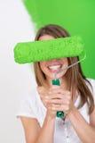 Mujer juguetona que oculta detrás de un rodillo de pintura Imagenes de archivo