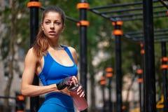 Mujer juguetona que presenta con la botella de agua en el gimnasio de la calle Fotos de archivo