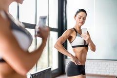 Mujer juguetona que presenta para el espejo Selfie que dobla los músculos fotografía de archivo