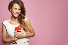 Mujer juguetona sonriente con un corazón rojo que celebra su aniversario o día de tarjetas del día de San Valentín en un fondo ro Foto de archivo libre de regalías
